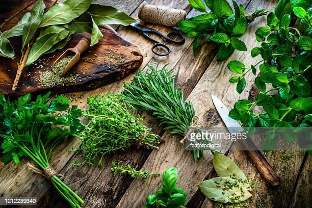 verse geurende organische kruiden voor het koken schot op rustieke keukenlijst - kruiden stockfoto's en -beelden