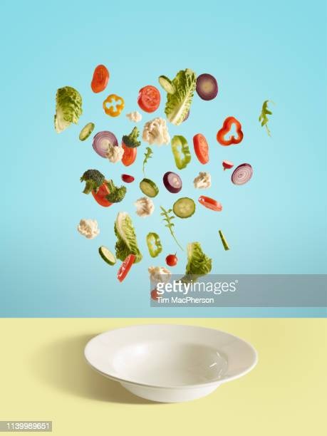 fresh sliced vegetables and salad leaf falling into bowl - in de lucht zwevend stockfoto's en -beelden