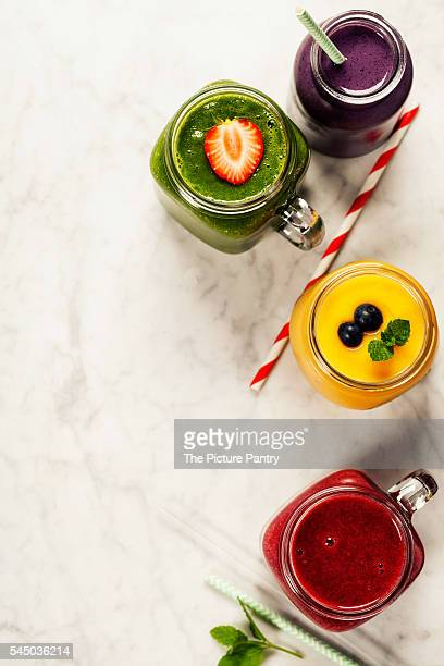 Fresh smoothies and fruits on marble table