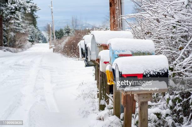 fresh snow covers mailboxes in a rural winter landscape. - diepe sneeuw stockfoto's en -beelden