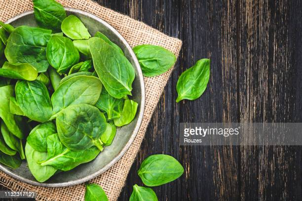 fresh spinach leaves in bowl on rustic wooden table - spinach stock pictures, royalty-free photos & images