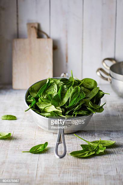 fresh spinach leaves in colander on wood - colander stock photos and pictures