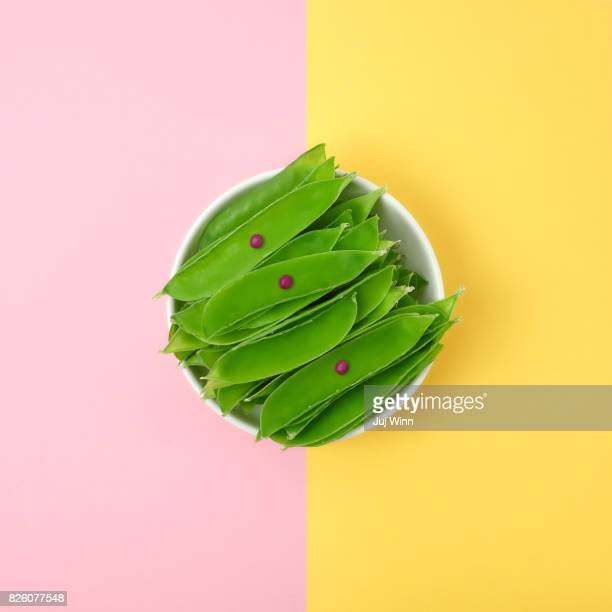 Fresh spring peas in a bowl on a color blocked background