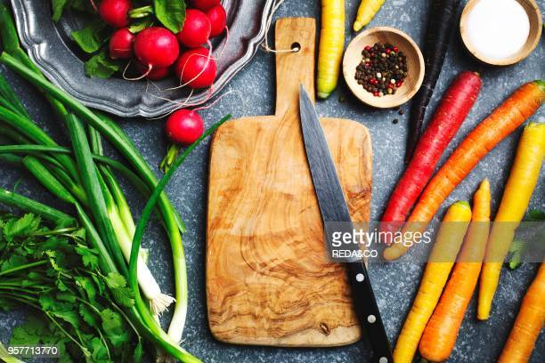Fresh spring vegetables around wooden cutting board with kitchen knife for vegetarian cooking top view