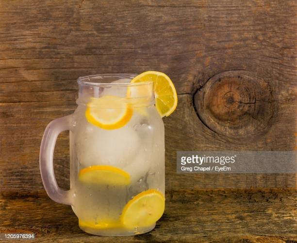 fresh squeezed lemonade in a mason jar cup with lemons and copy space. - lemon soda stock pictures, royalty-free photos & images