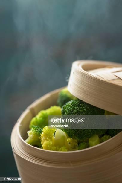 抽象的な青/ターコイズ色の風化した木製の素朴なテーブルの背景に竹の点心蒸し器で新鮮な蒸しブロッコリー。 - 蒸し ストックフォトと画像