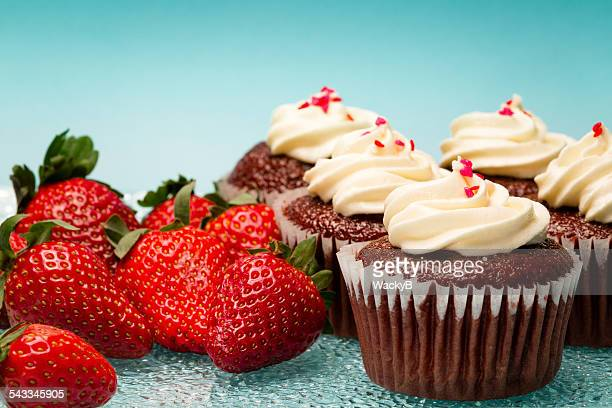 Fresh strawberries and red velvet cupcakes with whipped cream