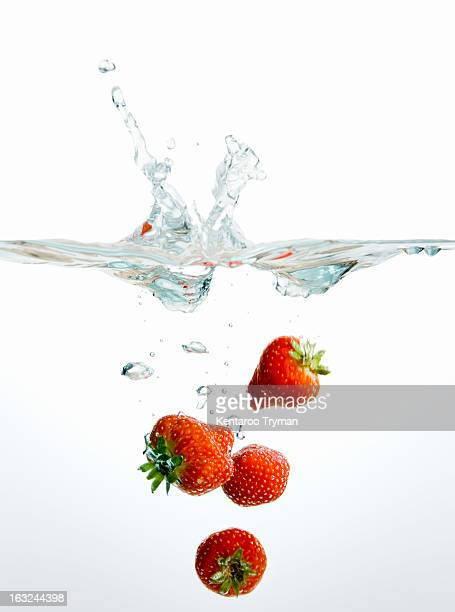 Fresh strawberries falling into water against white background
