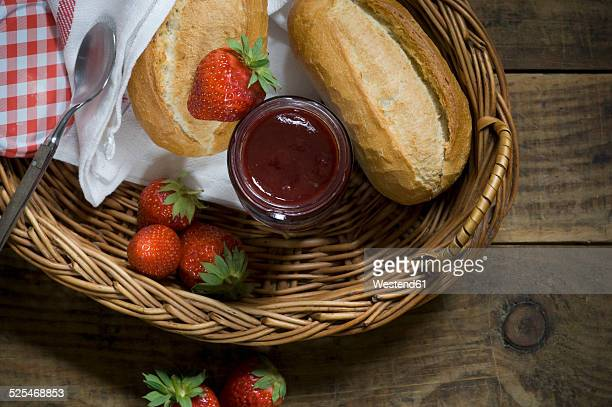 Fresh strawberries, strawberry jam and wheat rolls in a basket