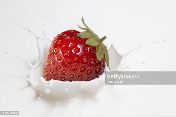 Fresh strawberry splashing onto milk surface