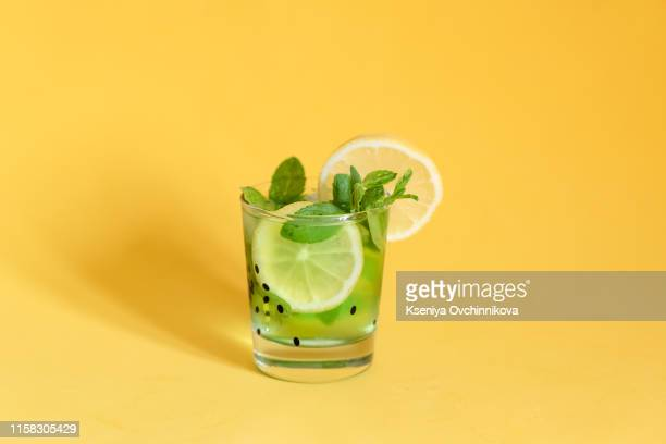 fresh summer fruits water or lemonade with lemon, orange and mint on yellow background. close up. - alcohol drink stock pictures, royalty-free photos & images