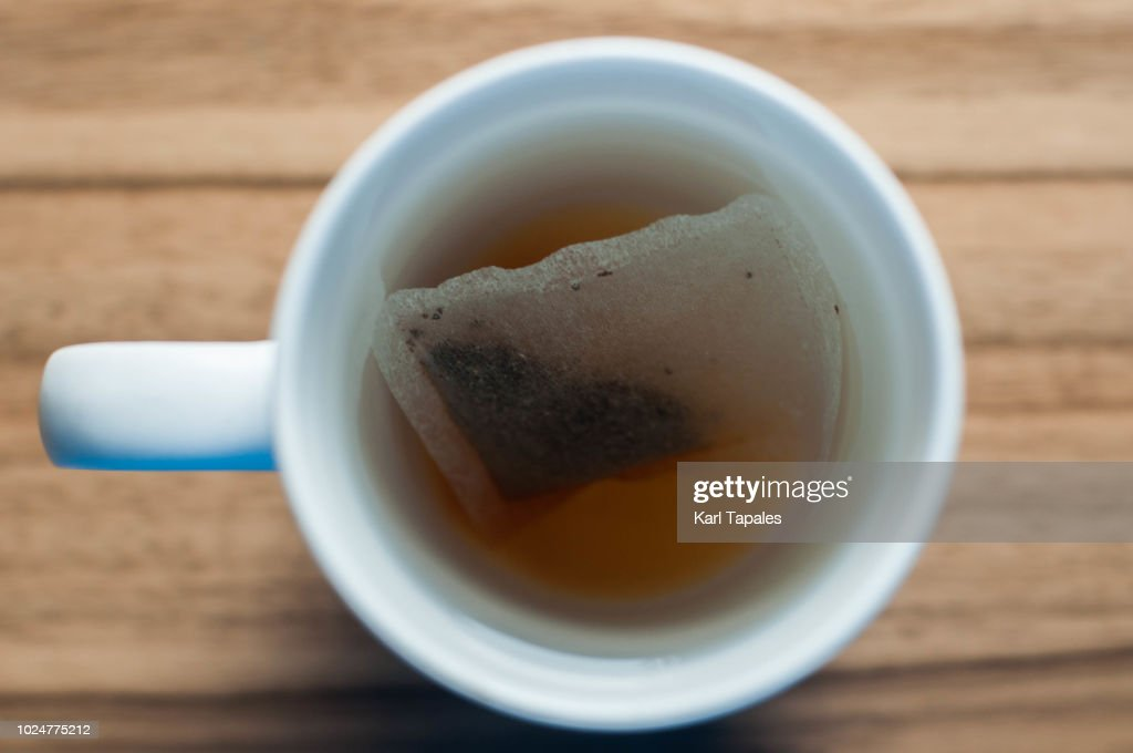 A fresh teabag in white mug with hot water : Stock Photo