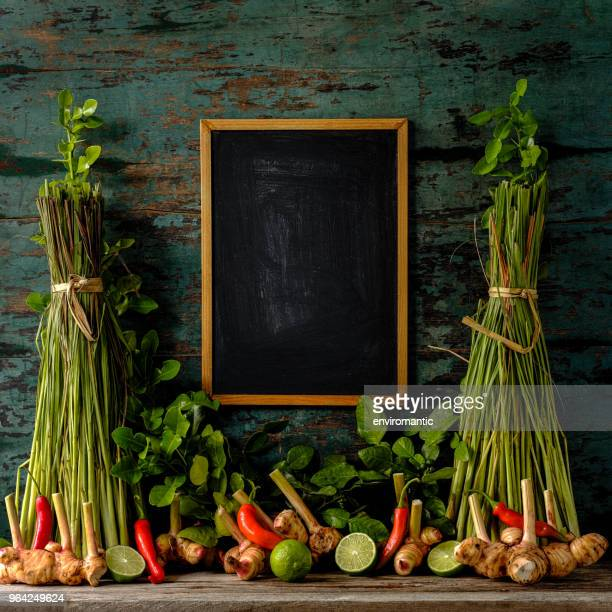 Fresh Thai Tom Yam soup herbs and spices against a turquoise colored wooden backgroun, with a wood framed blackboard in the middle between bunches of lemongrass.