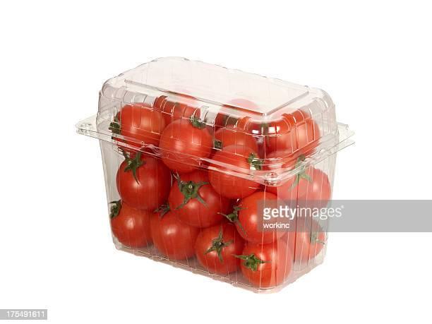 Tomates frescos en una caja de plástico