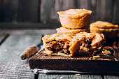 Fresh Traditional Australian meat mini pie on the wooden board on table background, closeup with copy space, rustic style