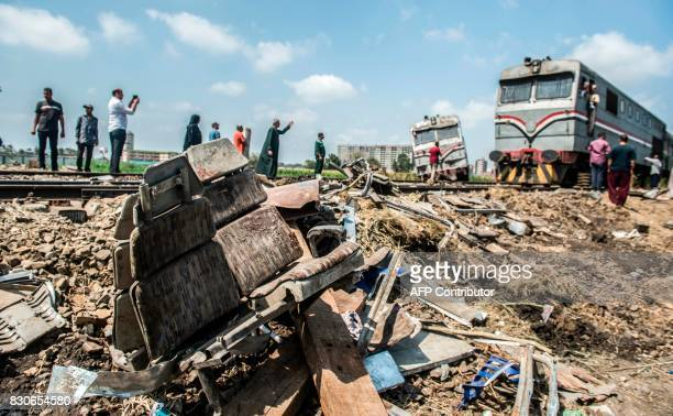 A fresh train passes by at the site of a fatal railroad collision from the day before in the area of Khorshid on the outskirts of Egypt's...