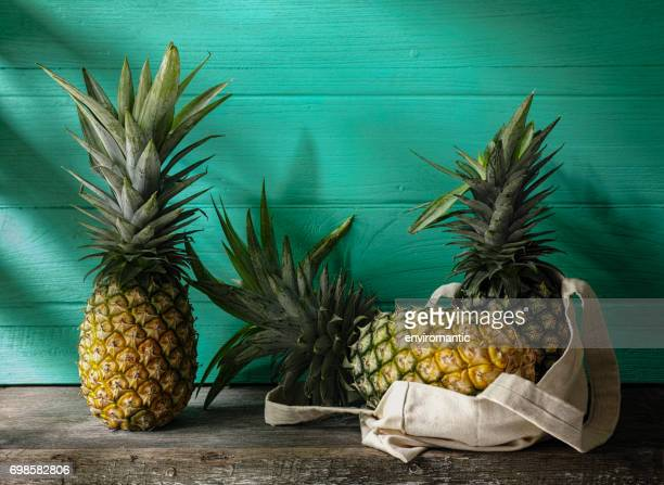 Frische tropische Ananas stehen neben mehr Ananas in eine wiederverwendbare Baumwoll-Tasche auf einem rustikalen Holztisch vor dem Türkis aus Holz ummauerten Hintergrund.
