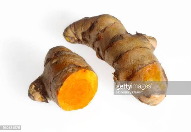 Fresh turmeric rhizomes showing orange inside on white