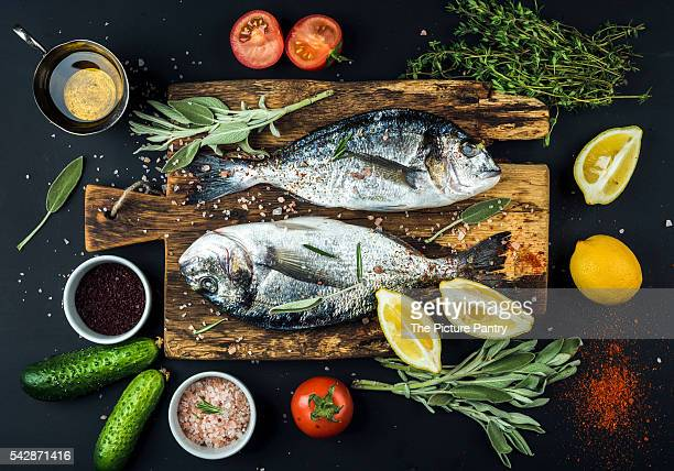 fresh uncooked dorado or sea bream fish with lemon, herbs, oil, vegetables and spices on rustic wooden board over black backdrop - dorado fish stock photos and pictures