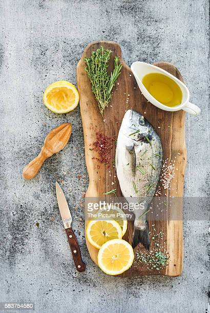Fresh uncooked dorado or sea bream fish with lemon, herbs, oil and spices on rustic wooden board over grunge backdrop