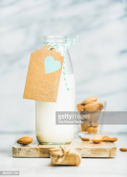 Fresh vegan dairy-free almond milk in glass bottle with craft paper label with copy space