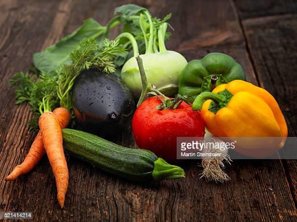 Fresh vegetables from market arranged at a wooden desk