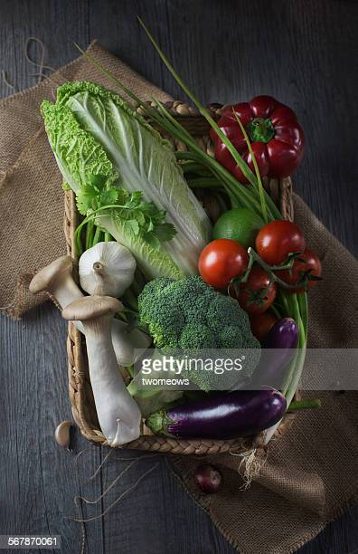 Fresh vegetables in basket on wooden table top.