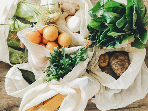 fresh vegetables in eco cotton bags on table in the kitchen. lettuce, corn, potatoes, apricots, bananas, rucola, mushrooms from market. zero waste shopping concept.   ban plastic 1034981638