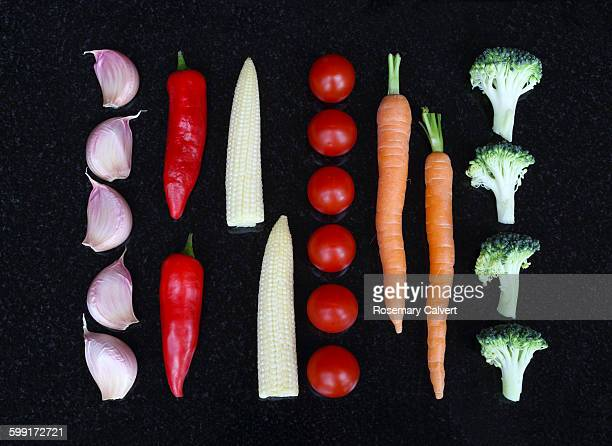 Fresh vegetables in parallel lines on black.
