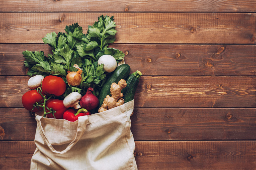Fresh vegetables in the eco cotton bag at the kitchen counter 1159567475