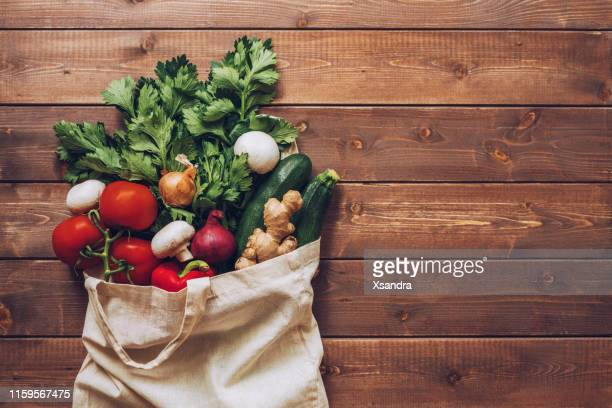 fresh vegetables in the eco cotton bag at the kitchen counter - flat lay stock pictures, royalty-free photos & images