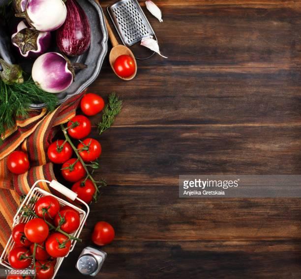 fresh vegetables on wooden table, top view. eggplants and tomato on wooden table. - rijp voedselbereiding stockfoto's en -beelden