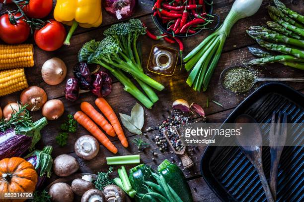 fresh vegetables ready for cooking shot on rustic wooden table - raw food stock pictures, royalty-free photos & images