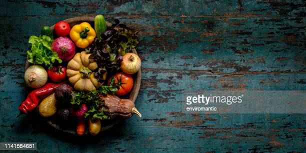 fresh vibrant colorful organic vegetables in an antique round wooden bowl on an old turquoise colored wood paneled table background, atmospheric rustic mood, with good copy space at the right of the image. - raw food diet stock pictures, royalty-free photos & images