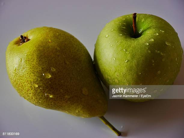 Fresh washed apple next to a pear, close up