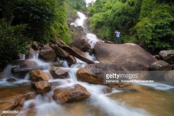 Fresh waterfall in the jungle with one man standing on the rock and take a photo