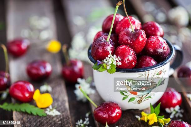 Fresh wet cherry in enamel metal mug, summer concept