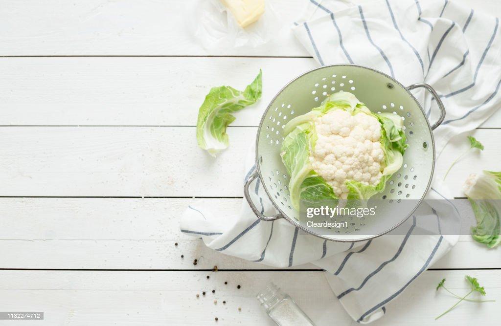 Fresh wet raw cauliflower in a strainer on rustic white : Stock Photo