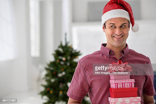 A fresh white building interior, flooded with light. Celebrating Christmas. A man in a Santa hat holding a stack of presents. Decorated Christmas tree.