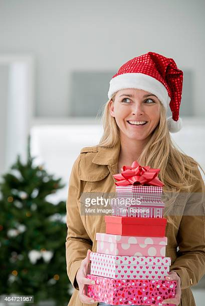 A fresh white building interior, flooded with light. Celebrating Christmas. A woman in a Santa hat holding a stack of presents. Decorated Christmas tree.