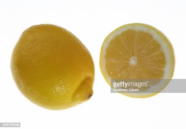 Fresh whole lemon and half a juicy lemon.