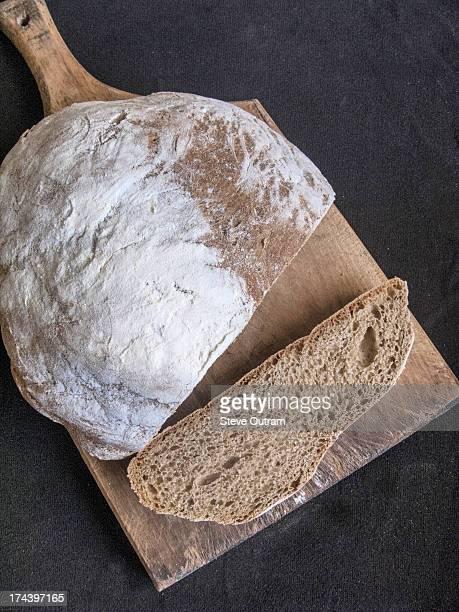 Fresh wholewheat brown loaf on bread board