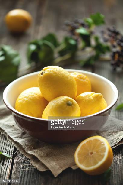 Fresh yellow lemons in a brown bowl on wooden table.