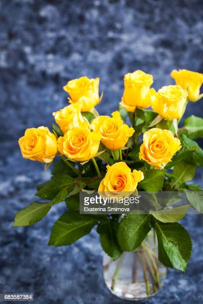 Fresh yellow roses flowers on blue painted wooden background