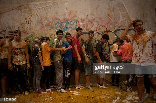 Freshers of the Faculty of Medicine line up covered with food during a hazing at the University of Granada in Granada on October 17 2013 AFP PHOTO/...