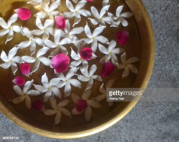 Fresh,floating flowers in a brass Uruli/vessel