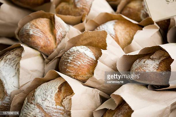 freshly baked bread in bags at a farmers market - loaf of bread stock pictures, royalty-free photos & images