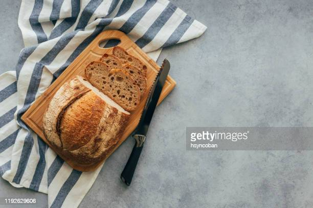 freshly baked bread on wooden table - bread stock pictures, royalty-free photos & images