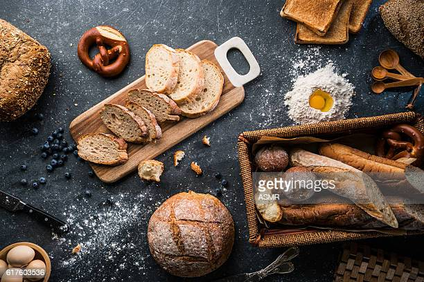 freshly baked bread on wooden table - freshness stockfoto's en -beelden
