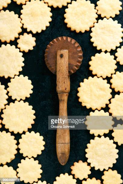 Freshly baked butter cookies with old wooden cutter wheel. Creative food concept.